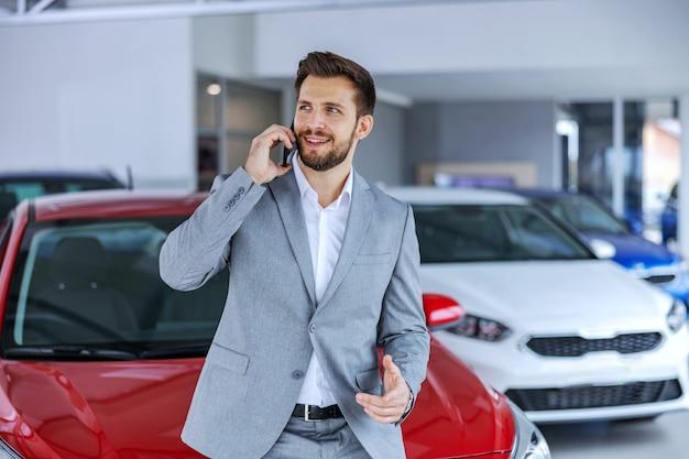 Cliente sorridente e feliz em pé no salão do carro e conversando com sua esposa. ele está se gabando do carro novo que comprou.