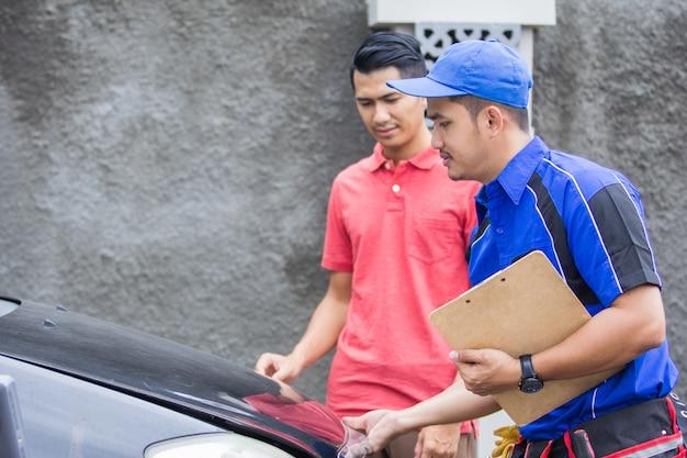 Cliente técnico da ajuda que fixa seu carro