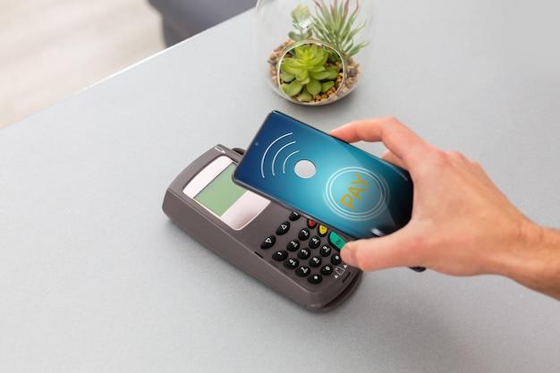 Cliente usando telefone celular para pagar por nfc