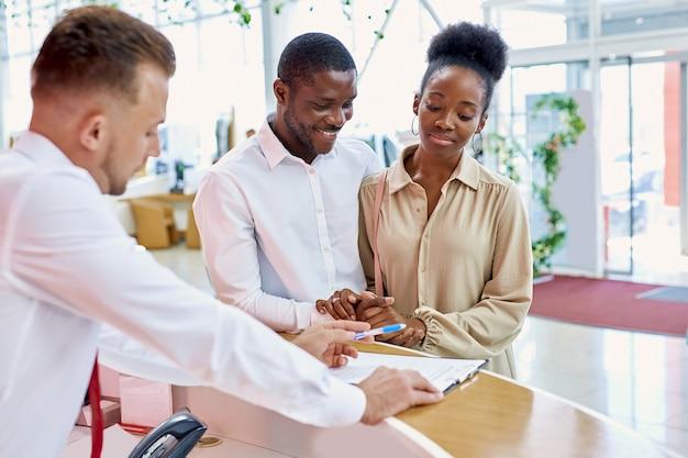 Clientes africanos assinando papéis com vendedor em loja da concessionária