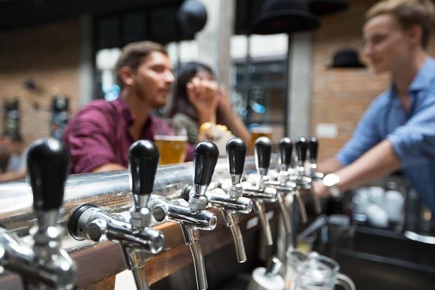 Clientes, bartender e beer taps no pub