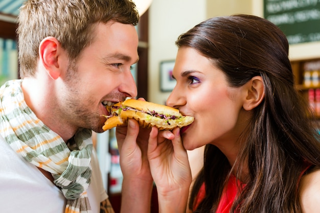 Clientes comendo cachorro-quente em lanchonete de fast food