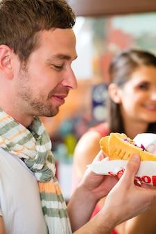 Clientes comendo hotdog na lanchonete fast food