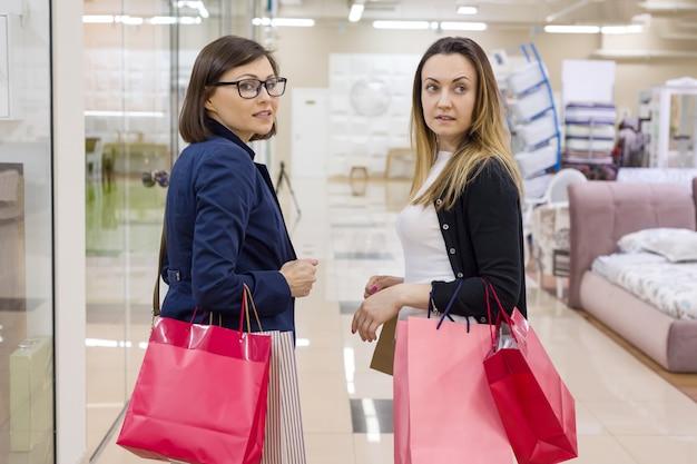 Clientes das mulheres com sacos de compras em uma alameda.