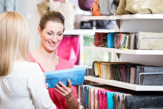 Clientes do sexo feminino em loja de compras à procura de carteiras e bolsas
