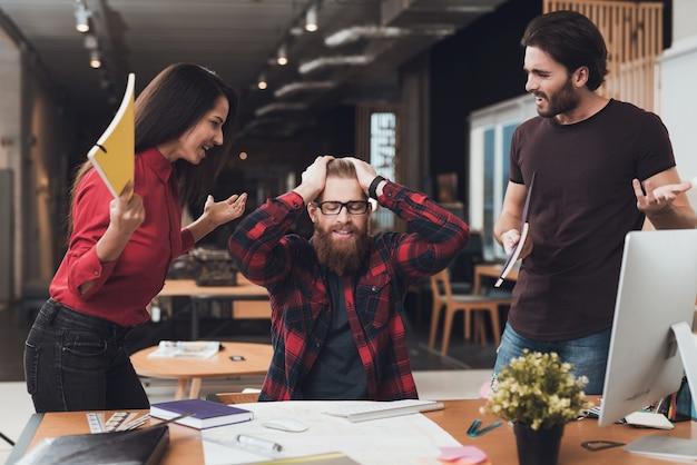 Clientes gritam para o designer em seu escritório.
