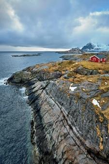Clif com casa de rorbu vermelho tradicional nas ilhas lofoten, noruega