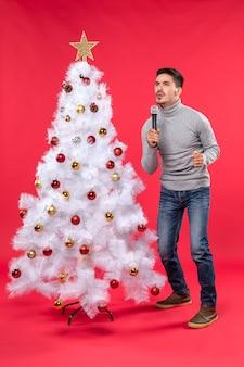 Clima de ano novo com cara positiva cantando uma música em pé perto da árvore de natal decorada em uma filmagem vermelha