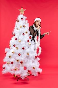 Clima de ano novo com linda garota em um vestido preto com chapéu de papai noel se escondendo atrás da árvore de natal