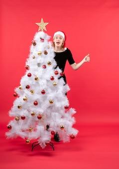 Clima de ano novo com uma jovem de vestido preto e chapéu de papai noel atrás da árvore de natal branca