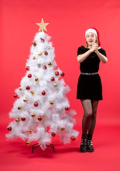 Clima de ano novo com uma jovem de vestido preto e chapéu de papai noel em pé perto da árvore de natal branca