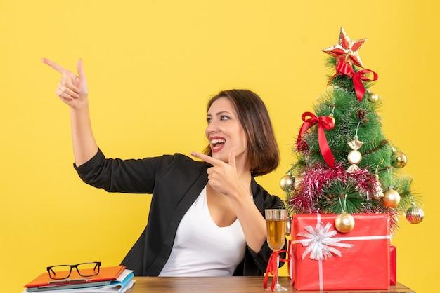 Clima de ano novo com uma linda mulher de negócios apontando algo feliz e sentada em uma mesa no escritório