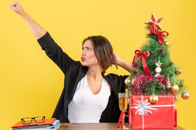 Clima de ano novo com uma linda mulher de negócios apontando algo surpreendente e sentada em uma mesa no escritório