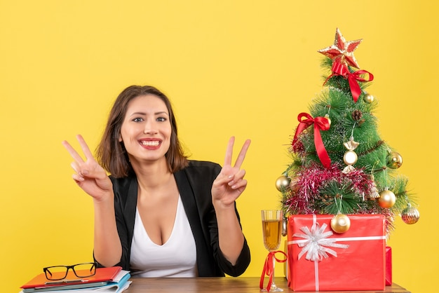 Clima de ano novo com uma linda mulher de negócios fazendo gesto de vitória com os dedos e sentada à mesa no escritório