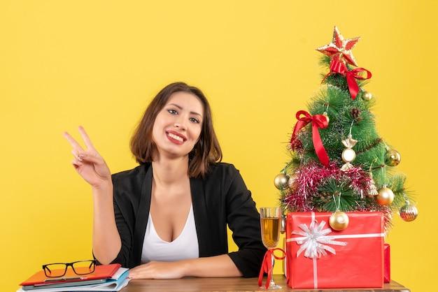 Clima de ano novo com uma linda mulher de negócios fazendo gesto de vitória e sentada à mesa no escritório