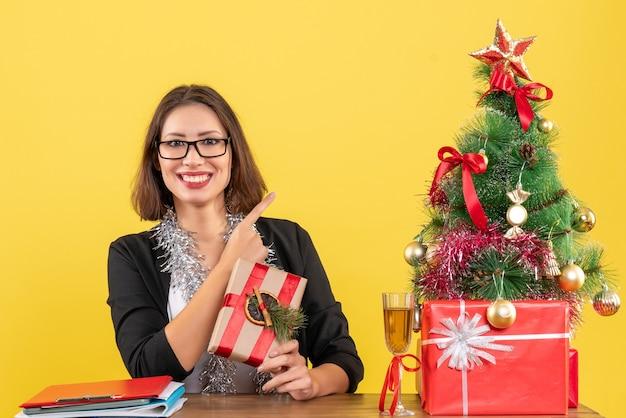 Clima de ano novo com uma linda mulher de negócios feliz de terno com óculos apontando para cima e sentada à mesa no escritório