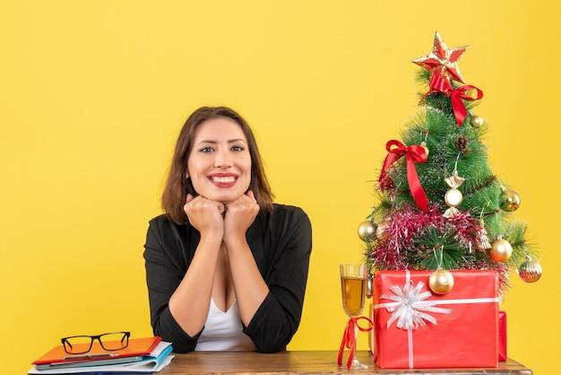 Clima de ano novo com uma linda mulher de negócios feliz e sentada à mesa do escritório