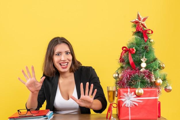 Clima de ano novo com uma linda mulher de negócios mostrando dez e sentada à mesa no escritório