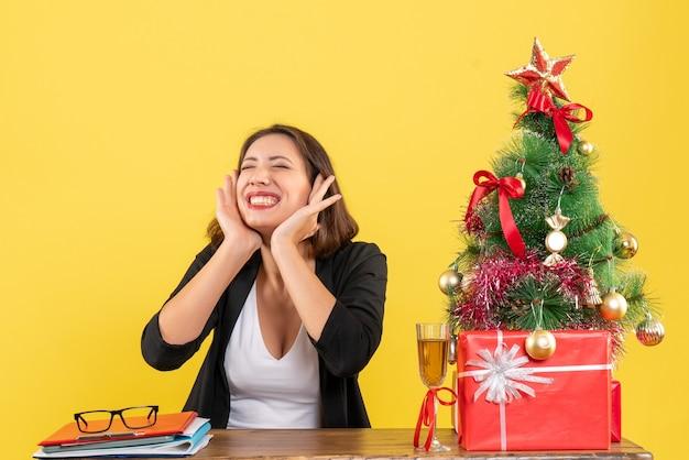 Clima de ano novo com uma linda mulher de negócios sentada a uma mesa no escritório