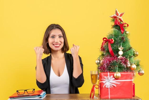 Clima de ano novo com uma linda mulher sorridente, feliz e sorridente, mostrando sua força e sentada em uma mesa no escritório