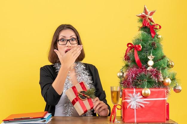 Clima de ano novo com uma linda senhora de negócios surpresa de terno com óculos e sentada à mesa no escritório