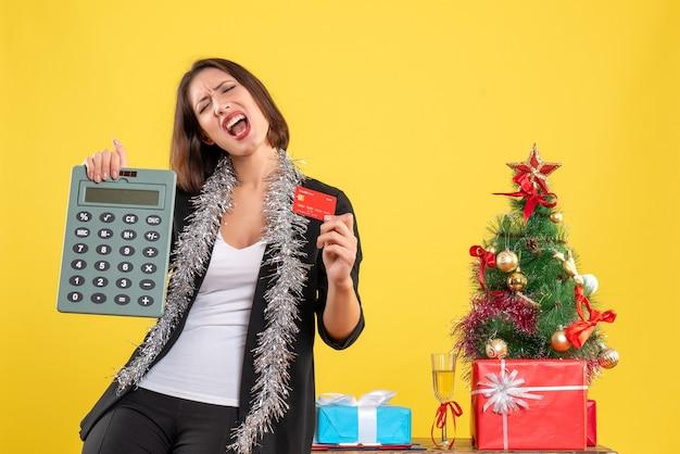 Clima de natal com a bela moça emocional em pé no escritório e segurando o cartão do banco da calculadora no escritório em amarelo