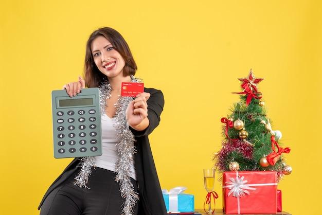 Clima de natal com a bela senhora sorridente em pé no escritório e apontando o cartão do banco da calculadora no escritório em amarelo