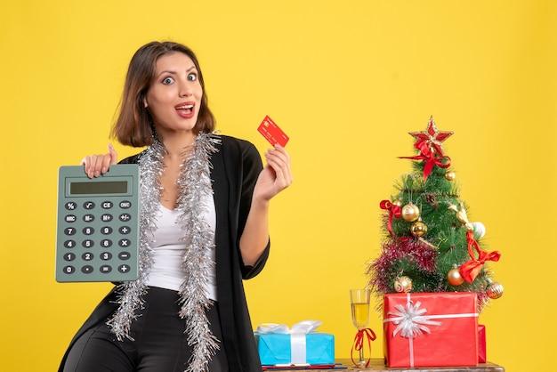 Clima de natal com a bela senhora sorridente em pé no escritório e segurando o cartão do banco da calculadora no escritório em amarelo