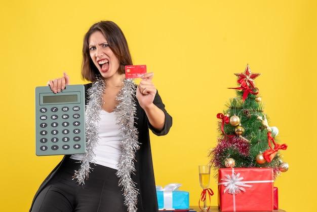 Clima de natal com a linda senhora nervosa em pé no escritório e segurando o cartão do banco da calculadora no escritório em amarelo