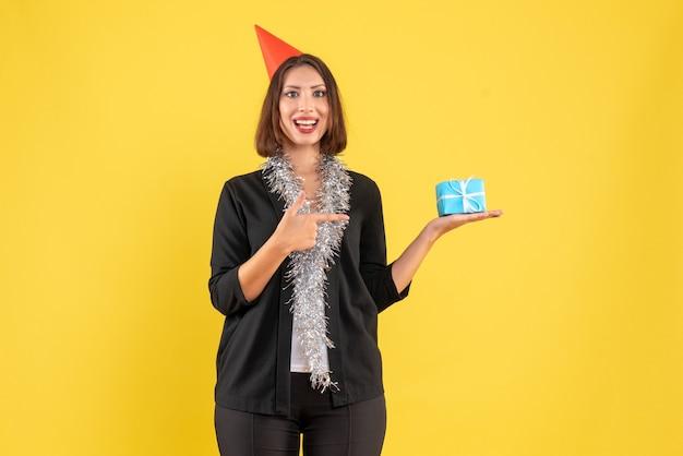 Clima de natal com a senhora de negócios positiva de terno com chapéu de natal e apontando o presente em amarelo