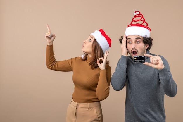 Clima de natal com animado casal legal confuso usando chapéu de papai noel vermelho cara mostrando o cartão do banco. mulher apontando para cima