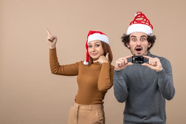 Clima de natal com casal animado e satisfeito com chapéu de papai noel vermelho cara mostrando cartão do banco, mulher fazendo gesto de me ligar