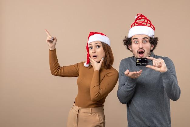 Clima de natal com casal animado e satisfeito com chapéu de papai noel vermelho, cara mostrando o cartão do banco, mulher apontando para cima