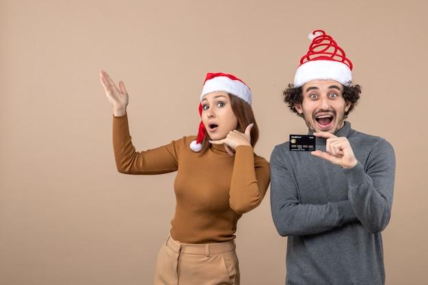 Clima de natal com casal animado e satisfeito com chapéu de papai noel vermelho mostrando cartão do banco e mulher fazendo gesto de me ligar