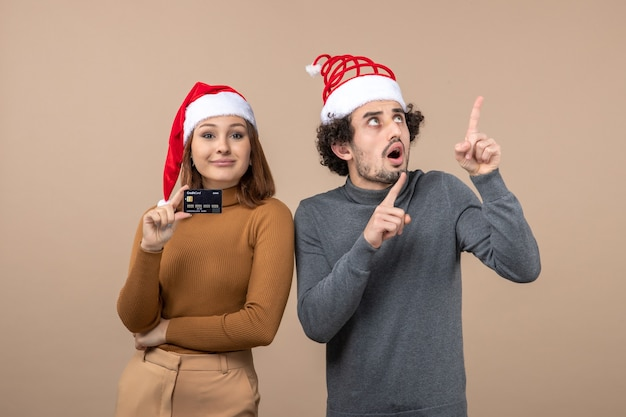 Clima de natal com casal animado e satisfeito com chapéu de papai noel vermelho, mulher mostrando cartão do banco