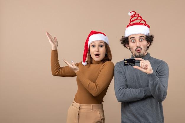 Clima de natal com casal animado satisfeito surpreso com chapéu de papai noel vermelho mostrando cartão do banco