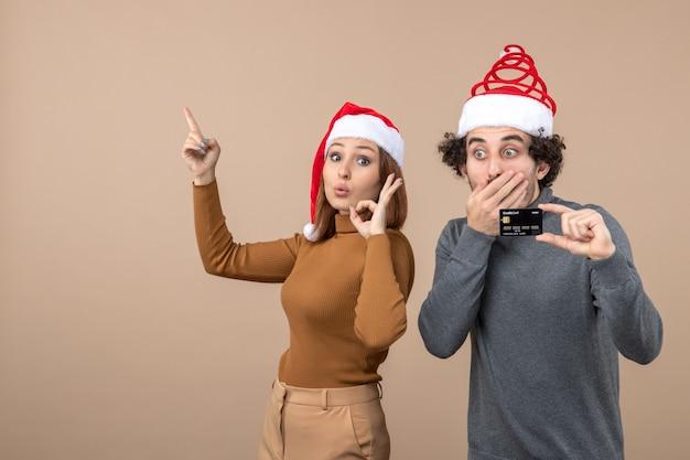 Clima de natal com casal legal animado vestindo cara de chapéus de papai noel vermelho mostrando cartão do banco. mulher apontando para cima