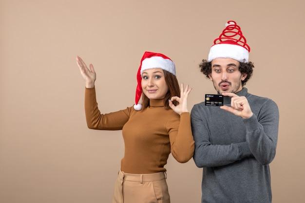 Clima de natal com casal legal satisfeito e animado usando chapéu de papai noel vermelho mostrando cartão do banco, mulher fazendo gesto de ok