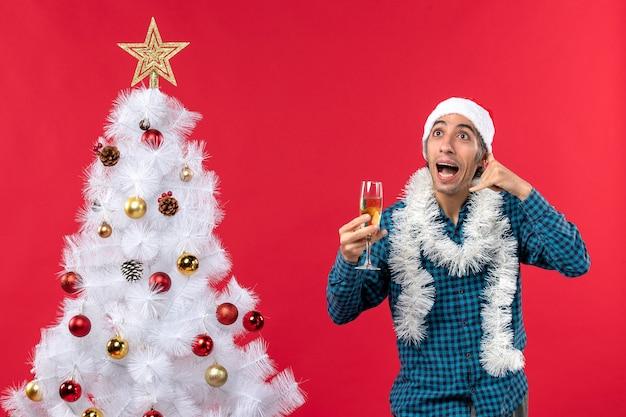 Clima de natal com jovem feliz com chapéu de papai noel em uma camisa azul listrada levantando uma taça de vinho e fazendo um gesto de me ligar perto da árvore de natal