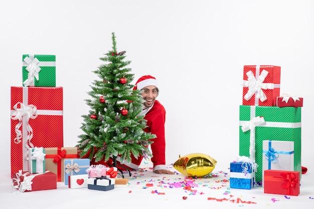 Clima de natal com o jovem papai noel se escondendo atrás de uma árvore de natal perto de presentes em cores diferentes em fundo branco