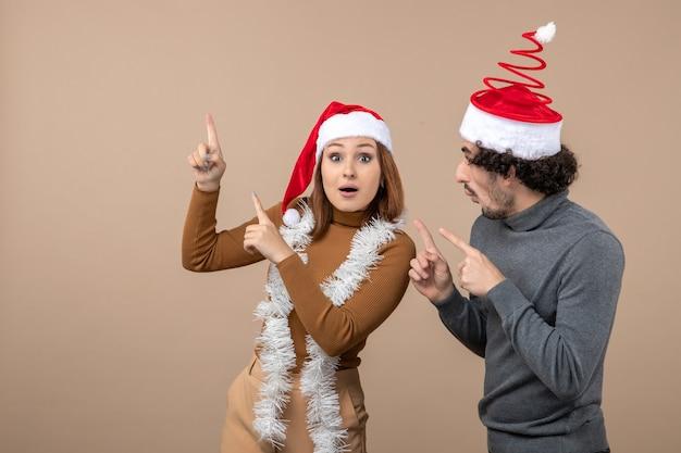 Clima de natal com um lindo casal animado e satisfeito com chapéu de papai noel vermelho apontando para cima