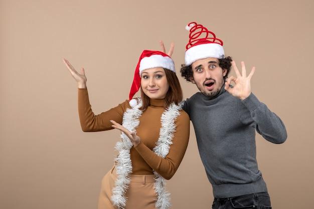 Clima de natal com um lindo casal animado e satisfeito usando chapéus vermelhos de papai noel