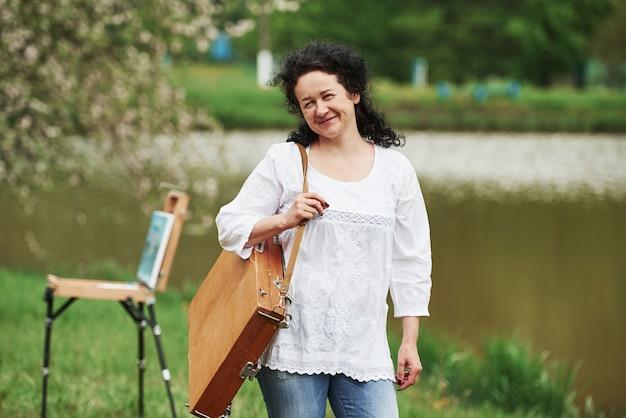 Clima de primavera. pintor maduro com caixa de instrumentos passeia no lindo parque
