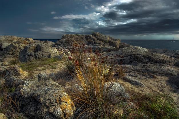 Clima de tempestade acima da costa rochosa amarelada de playa de aro