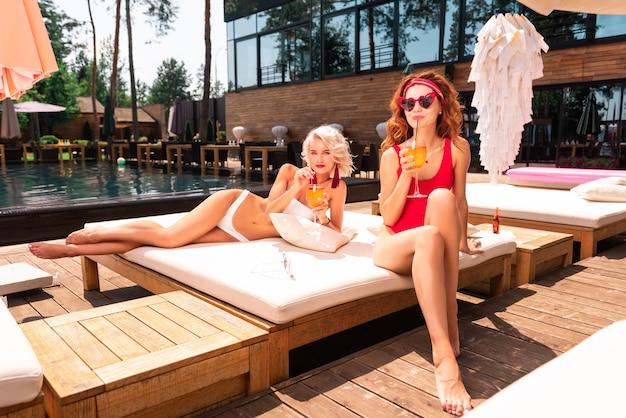 Clima de verão. mulheres alegres e positivas bebendo coquetéis enquanto relaxam em uma cama de praia