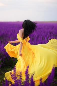 Clima de verão. uma mulher com um vestido amarelo luxuoso está de pé em um campo florido roxo, de costas para a câmera.