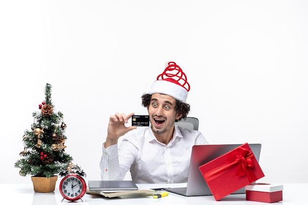 Clima festivo de feriado com empresário chocado com chapéu de papai noel e olhando para o cartão do banco no escritório em fundo branco
