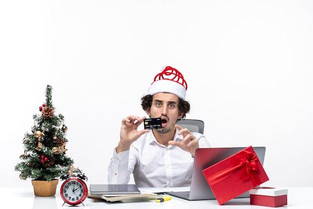 Clima festivo de feriado com empresário chocado com chapéu de papai noel e segurando o cartão do banco no escritório em fundo branco
