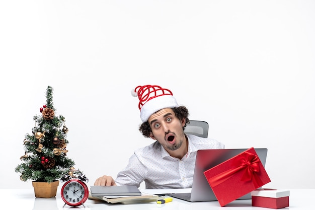 Clima festivo de feriado com empresário chocado com chapéu de papai noel trabalhando sozinho no projeto no escritório em fundo branco