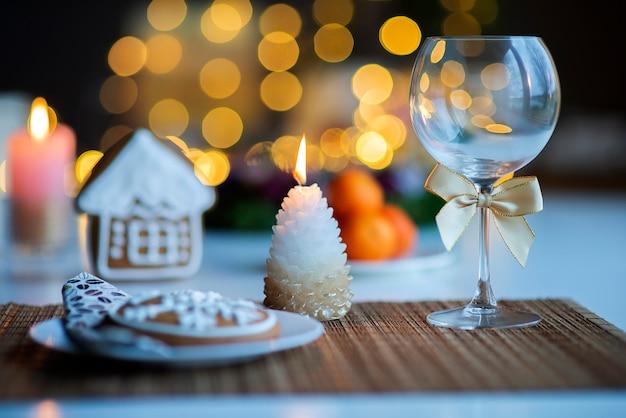 Clima festivo de natal com uma taça de vinho e uma vela acesa na mesa de jantar da cozinha